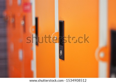 Locker in orange, orange metal storage cabinet, A close-up orange locker, The orange locker has many numbers, Close-up locker #1534908512