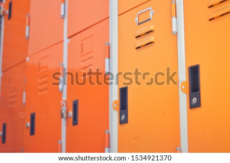 Locker in orange, orange metal storage cabinet, A close-up orange locker, The orange locker has many numbers, Close-up locker #1534921370