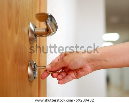 stock photo : Locking up or unlocking the door with a key in hand