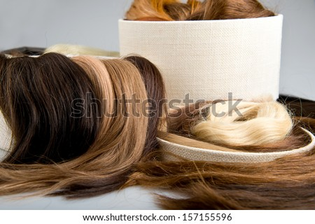Locks of faux hair for beauty saloon different colors and structure in box. Blond, red and brunette on gray background