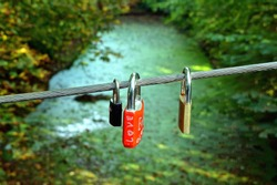 Locks of love in the shape of a heart hang on a steel cable of a pedestrian bridge, green water, river background. Padlocks, love locks lettered with love