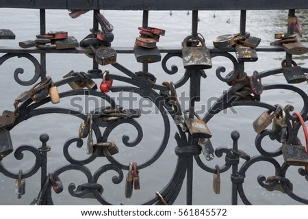 Locks of various sizes, shapes and colors locked on a black metal fence by couple to celebrate love and marriage or to make a wish. The background is the Iset River in Yekaterinburg Russia. #561845572