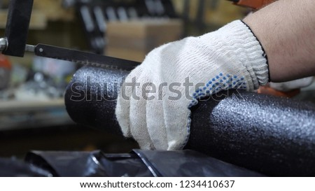 locksmith in protective gloves saws black pipe with hacksaw. man works in manufactory. close-up