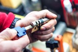 locksmith is testing door lock cylinder with key