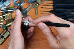 Locksmith picks a cylinder lock with lockpick and tension wrench