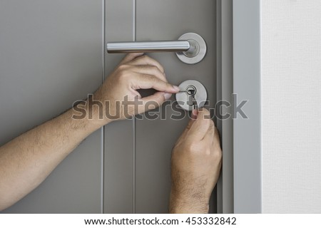 locksmith try to fix a key lock door for open it by screwdriver and tools - can use to display or montage on product