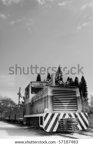 Locomotive of discard under sky in black and white tone.