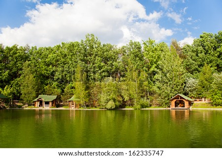 Lodge on the shore of the lake, surrounded by green trees. Nice place to relax.