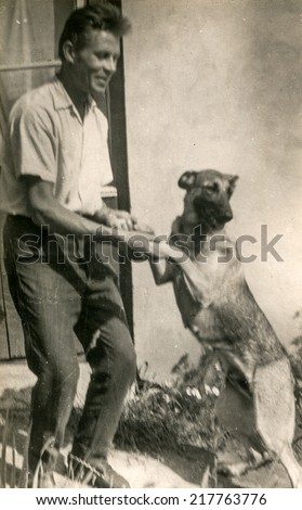LODZ, POLAND, CIRCA FIFTIES - Vintage photo of man with a dog