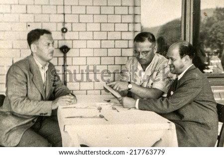 LODZ, POLAND, CIRCA FIFTIES - Vintage photo of three man studying menu in restaurant