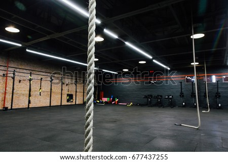 Loft big empty interior of the gym for fitness workout. Cross power training. Nobody, ropes, rowing and power rack pull-up. Stylish modern design for hipsters. Black floor and walls, red brick wall.