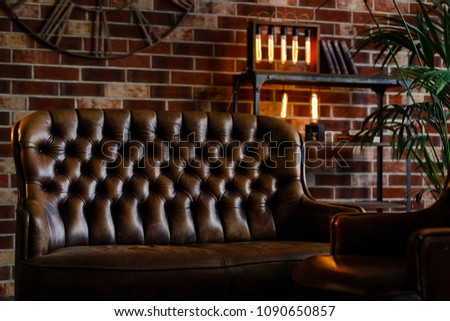 Loft interior. Leather couch and armchair in a dark room #1090650857