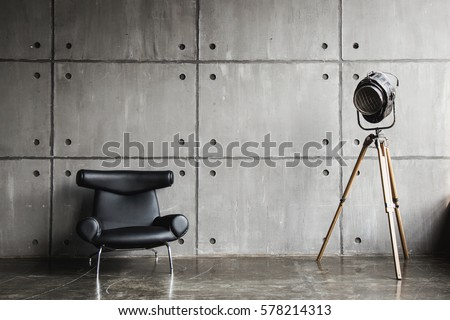 Loft interior mock up photo. Grey block wall with leather black chair and vintage light source lamp. Background photo with copy space for text.