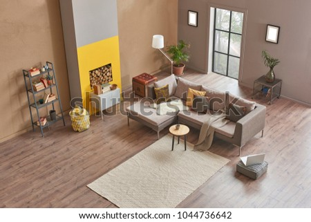 Loft living room and modern home design interior. Grey an brown background wit fireplace and wood concept.
