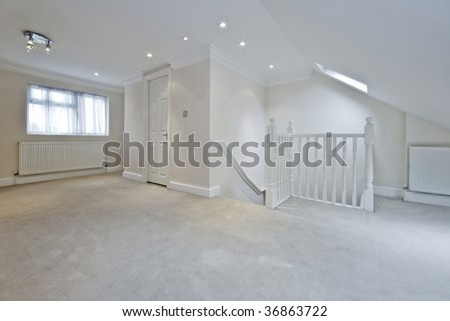 loft room with suite bath room and stairs with white wooden rails