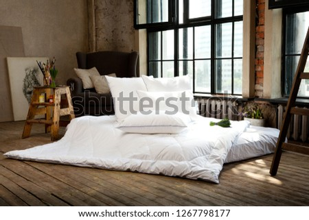 Loft style bedroom interior design. White blanket and pillows. Flowers. Paint brushes. Armchair. Wooden floor.
