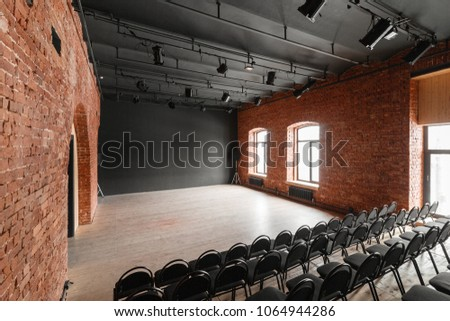 Loft style. Hall with black chairs for webinars and conferences. A huge room with large Windows, surrounded by brickwork, and parquet floors. For film and theatre productions #1064944286