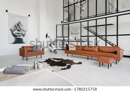 Loft style interior in house with modern living room, bath in bathroom, comfortable couch, pillows on leather armchair, painting on wall and scooter on concrete floor with skin carpet