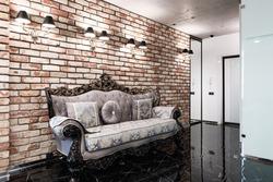 Loft stylised interior in studio apartment. Vintage bricked wall and sofa.