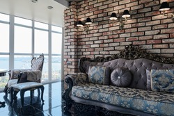 Loft stylised interior in studio apartment. Vintage bricked wall, chairs and sofa.