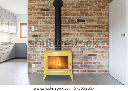 Loft with red brick wall and yellow freestanding stove Stock fotó ©
