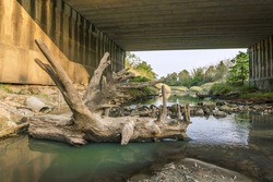 log at Under the bridge : Peaceful and Tranquil nature - river flowing through natural cascades and wet rock and sand with sunlight shining.