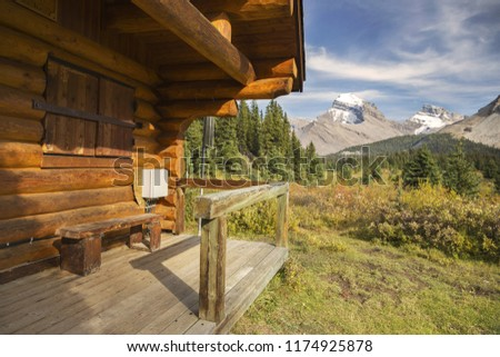 Log Cabin and Distant Snowy Rocky Mountain Tops in Red Deer River Valley, Banff National Park, Canadian Rocky Mountains