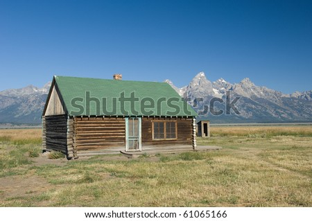 Log Cabin at the Grand Tetons An old log cabin and outhouse sit along on a prairie in Western Wyoming against the backdrop of the Grand Tetons mountain range.
