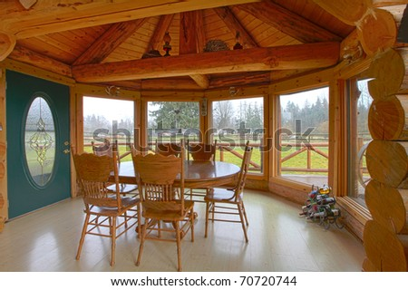 Log cabin breakfast area with dining room table and farm view