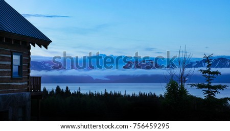 Log cabin house with view of mountains, forest, glacier, in Alaska