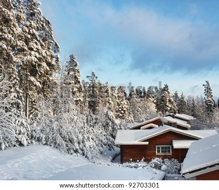 Log cabin houses in snowy winter forest scenery