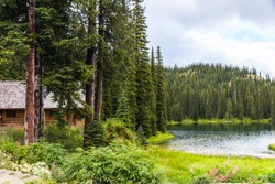 Log Cabin in Pine Forest by Lake. Bridal Lake, Kootenay Rockies, British Columbia.