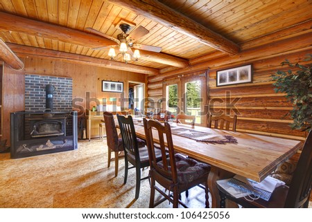 Log cabin rustic living room with large table and stove.