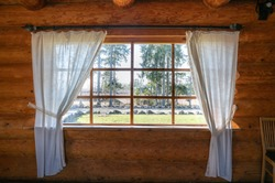 Log cabin window. Looking through the window from inside. Nature behind window glass. Window frame and curtain. Triangle. Timber construction. Wooden, log hut. Warm wooden shack. Sunny weather