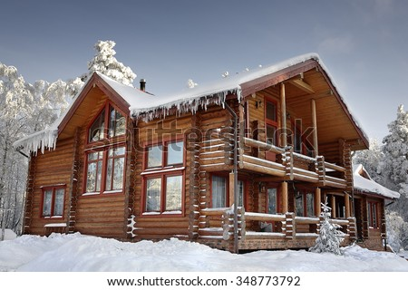 Log cabin with large windows, balcony and porch, modern house design, snowy winter, sunny day. #348773792