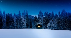 Log cabin with shining window in wintry forest