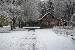 log cabin with snow falling and snow on the ground