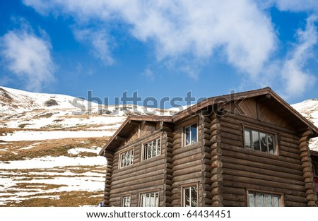 Log cabin with snow mountain behind