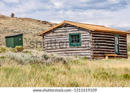 Log home with green trim basking in the sun with a green outhouse in the yard