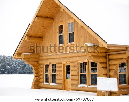 Log house covered in snow during winter