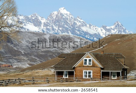 Log house on prarie with snow covered Gand Teton mountains in background