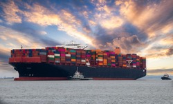 Logistics and container loading by large barges by sea in a harbor full of containers waiting to be transported