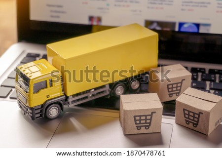 Logistics, and delivery service - Truck and paper cartons or parcel with a shopping cart logo on a laptop keyboard. Shopping service on The online web and offers home delivery.  Foto stock ©