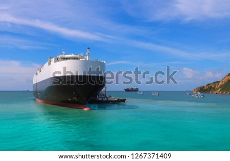 Logistics and international shipping car vessels, ocean freight transportation by tugboat assisting the vessel to the port on blue sky background. #1267371409