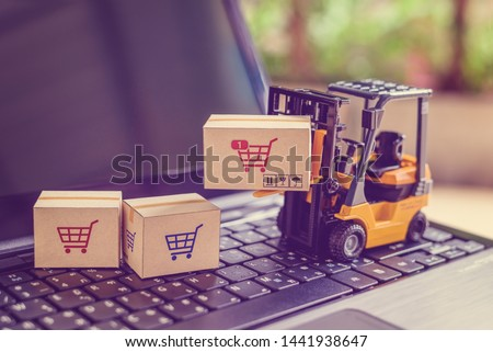 Logistics and supply chain management for online shopping concept : Fork-lift moves a box with a red shopping cart logo, 2 cartons on a laptop computer, depicts delivering goods or products in a store