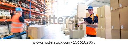 logistics and transport workers in a warehouse with goods for storage and dispatch - scanning a parcel