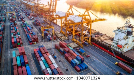 Logistics and transportation of Container Cargo ship with working crane bridge in shipyard at sunrise, Shipping cargo to harbor Aerial view from drone, International transportation, Business logistics