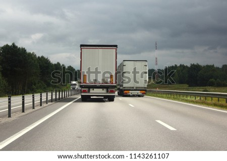 Logistics, international freight by road-two white trucks drive next to the two-lane asphalted country road in the summer day, rear view #1143261107
