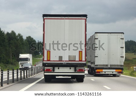 Logistics, international freight by road-two white trucks drive next to the two-lane asphalted country road in the summer day, rear view #1143261116