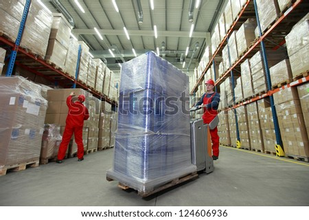 logistics management of the flow of resources two workers in uniforms and safety helmets working in storehouse